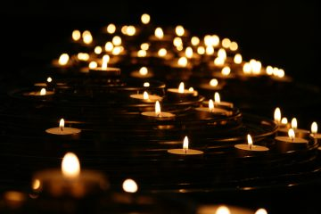 Numerous lit tea lights in a dark room bringing small pieces of light and hope into grief and loss