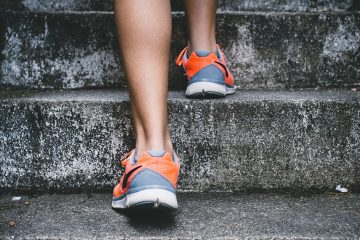 Back of a woman's ankles running up steps in trainers because she feels energised and practices self-care because she had transformational coaching