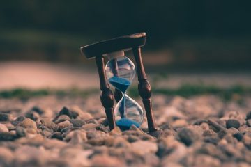 An hourglass resting upright on gravel with the sand pouring through showing time passing