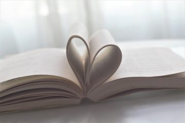 Open book with some pages turned inwards to create a heart shape as our values come from the heart