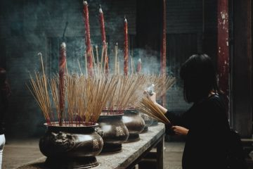 Woman burning incense in a Buddhist temple taking time to ask for help
