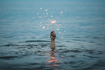 A hand reaching out of the water holding a sparkler because sometimes we can feel lost and alone and need to signal for help