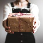 Woman holding a wrapped gift in front of her as a symbol of giving and receiving