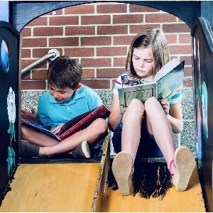 Young girl and boy sitting reading books to find out why things are the way they are